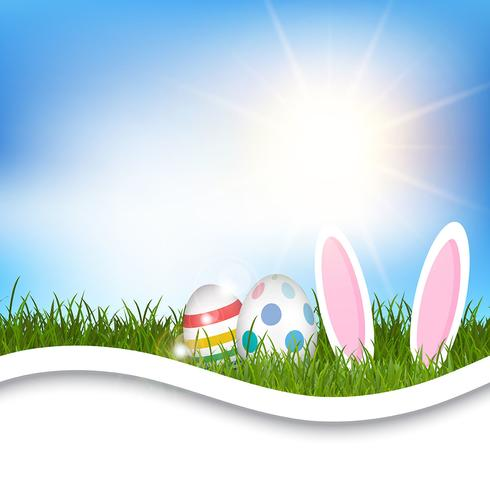 Easter background with eggs and bunny ears in grass