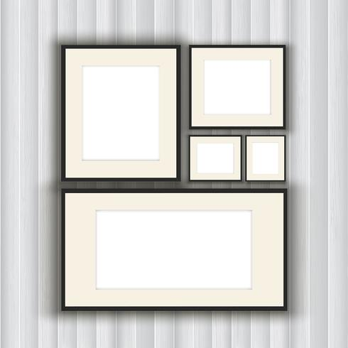 Blank picture frames on a wooden wall background