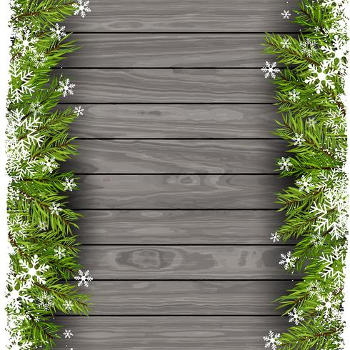Christmas tree branches on wood background