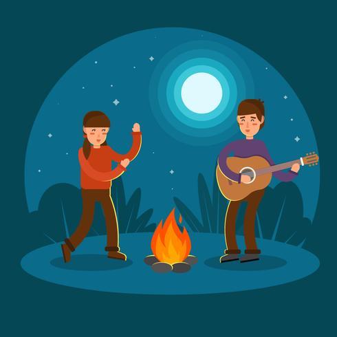 Jong koppel gitaar spelen en dansen op kampvuur