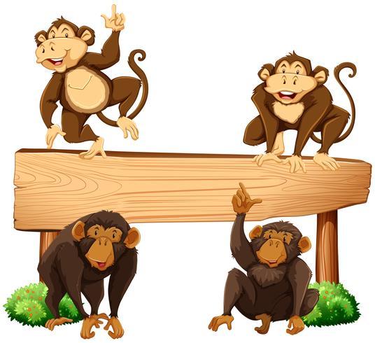 Cuatro monos y cartel de madera.