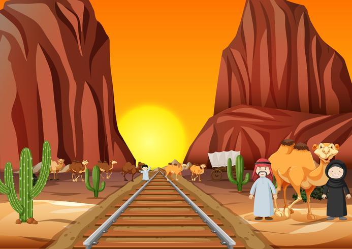 Kamelen en Arabische mensen oversteken van de spoorlijn bij zonsondergang