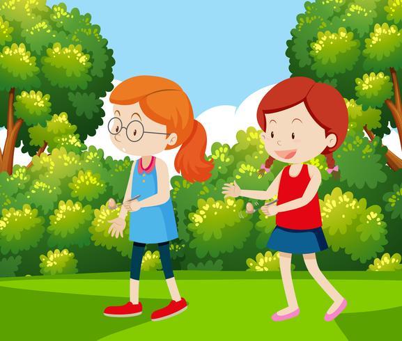 Dos chicas haciendo una carrera de huevos y cucharas.