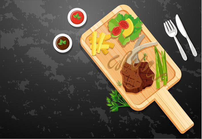 Lambchop and vegetables on wooden board