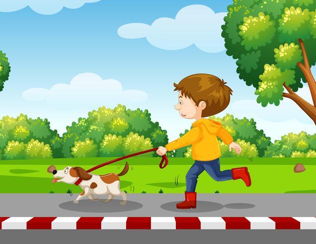 jonge jongen die een hond loopt