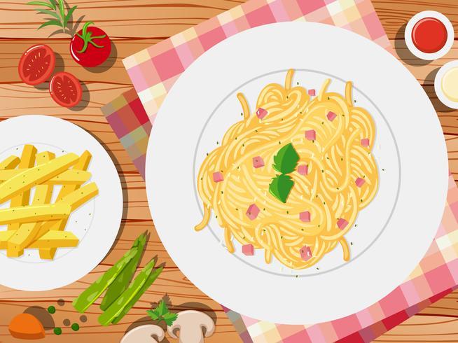 Espaguete e frenchfries na mesa