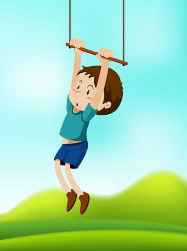 Um menino pendurado no balanço