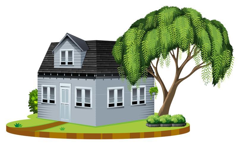 Graues Haus mit großem Baum im Rasen