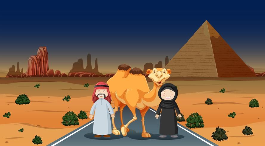 Två människor och kamel i öknen