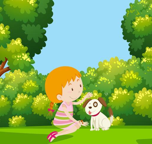 Tjej leker med hund i trädgården