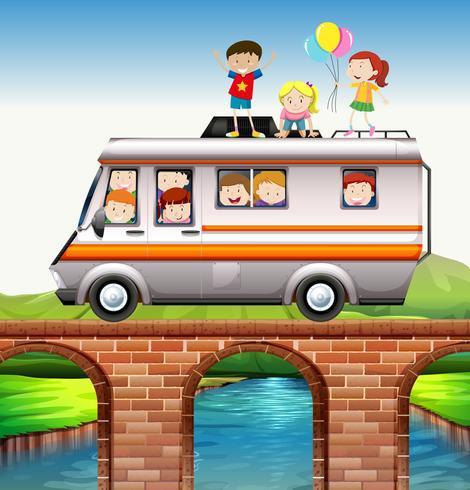 Children riding on camper van over the bridge