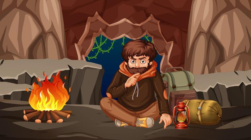 Un hombre acampando en una cueva.
