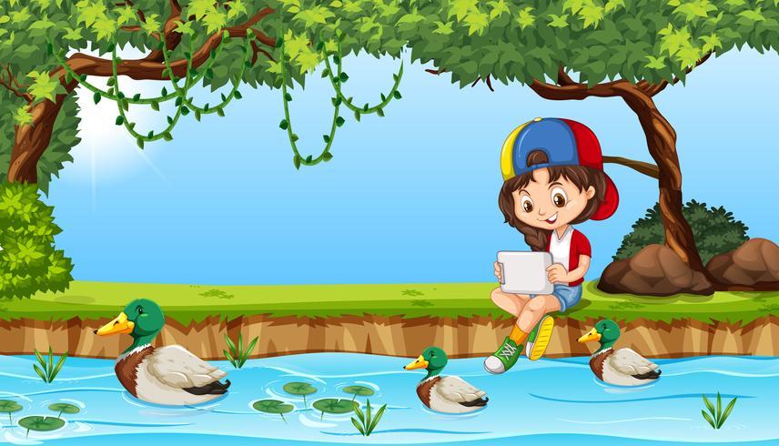 Junges Mädchen auf dem iPad nahe Teich