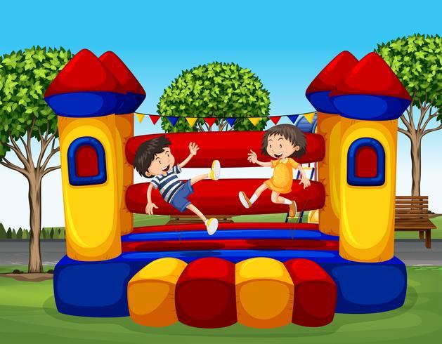 Due bambini che rimbalzano sulla casa di gomma vettore