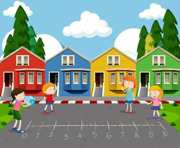Niños jugando frente a casas coloridas vector