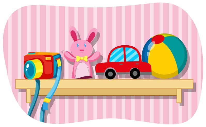 Cámara y otros juguetes en estante de madera.