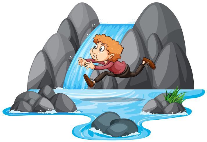 Un garçon sautant sur le rocher