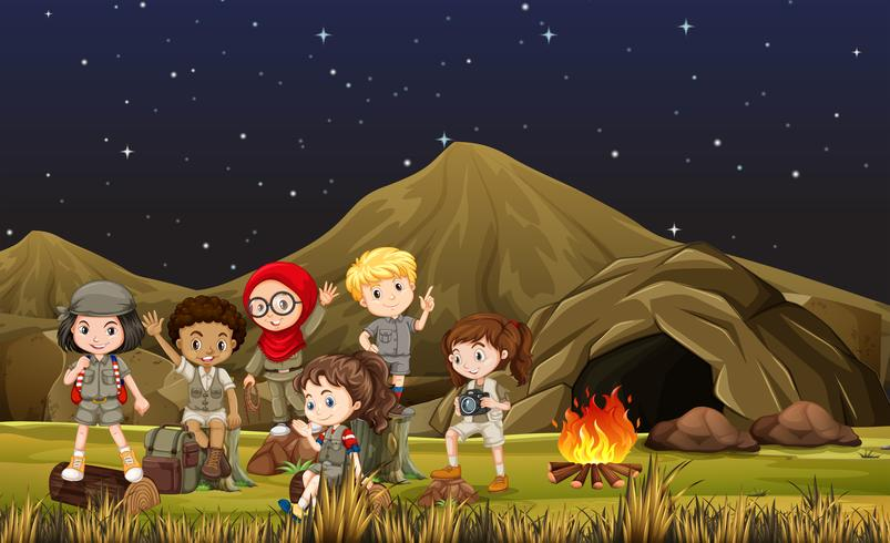 Niños disfrazados de safari acampando junto a la cueva.