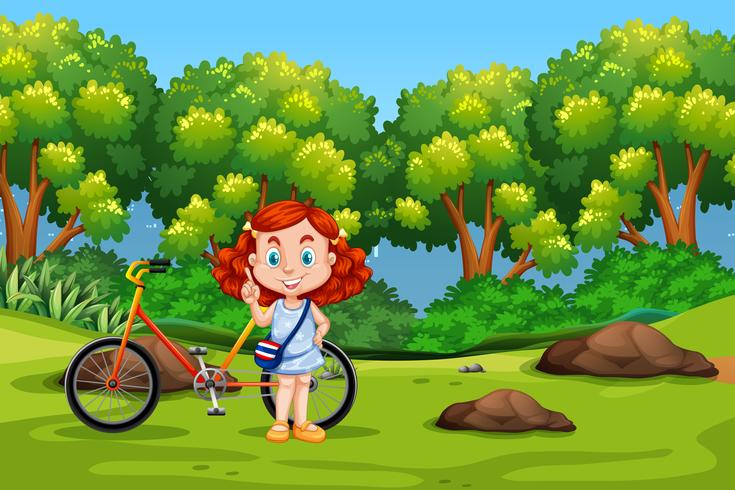 Una niña tailandesa montando bicicleta en el parque