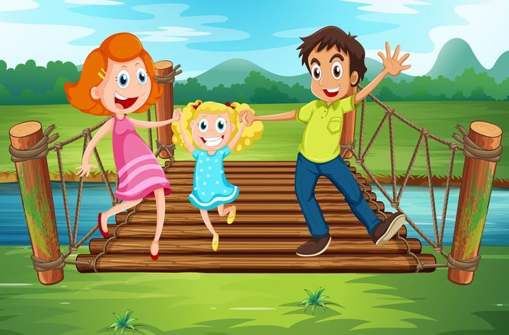 Familj på träbroen i parken