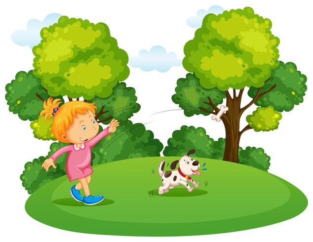 Fille jouant avec un chien dans un parc