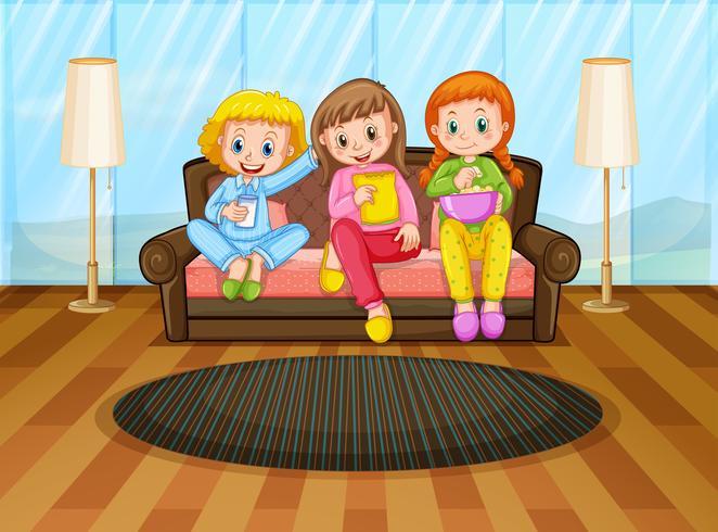 Trois filles mangeant des collations dans le salon
