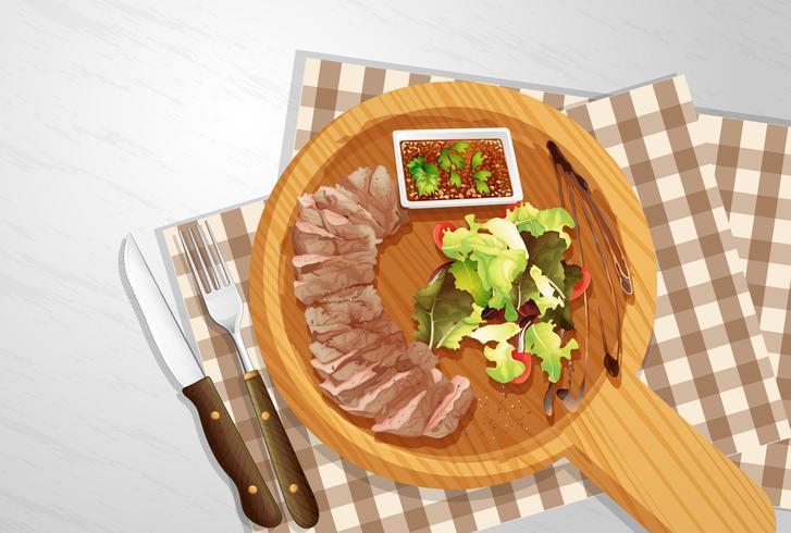 Bistecca e insalata su tavola di legno