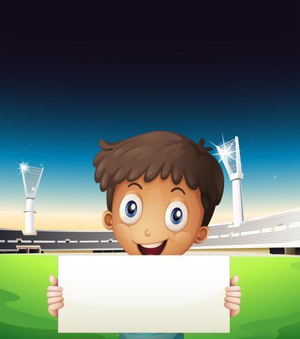 Ein Junge im Stadion, der eine leere Pappe hält