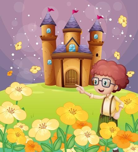Ein Junge, der nahe den Blumen im Hügel mit einem Schloss zeigt