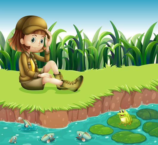 Una niña con un sombrero sentado en la orilla del río vector