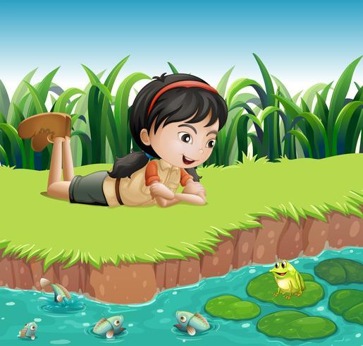 Una niña al lado de un estanque