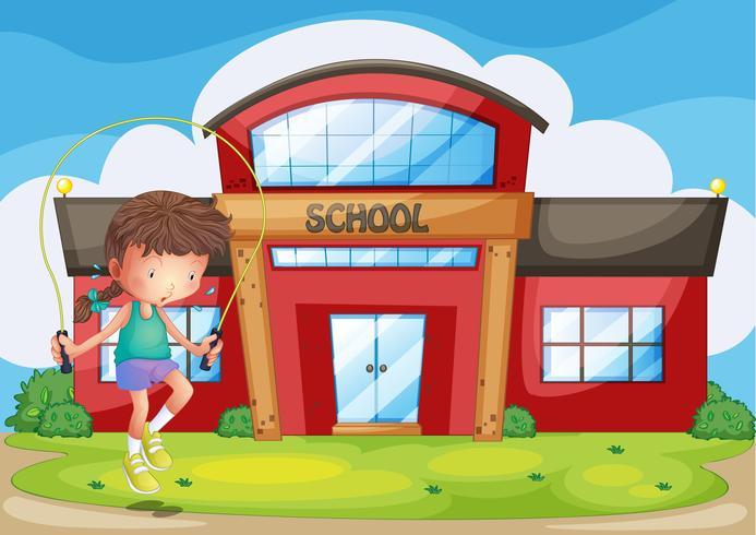 Una niña jugando frente a la escuela.