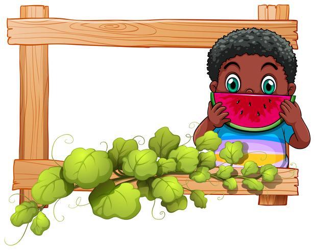 Ein Holzrahmen mit einem Jungen, der Wassermelone isst