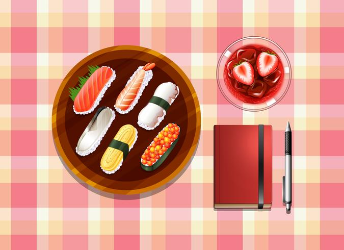 Una mesa con sushi, un cóctel, un bolígrafo y un cuaderno.