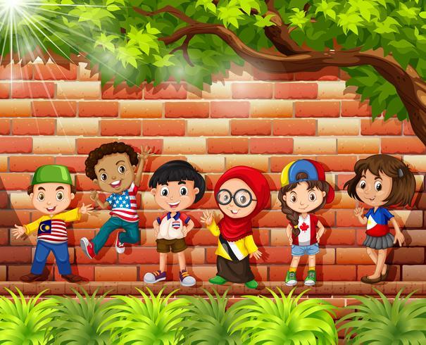Bambini provenienti da diversi paesi in piedi sotto l'albero