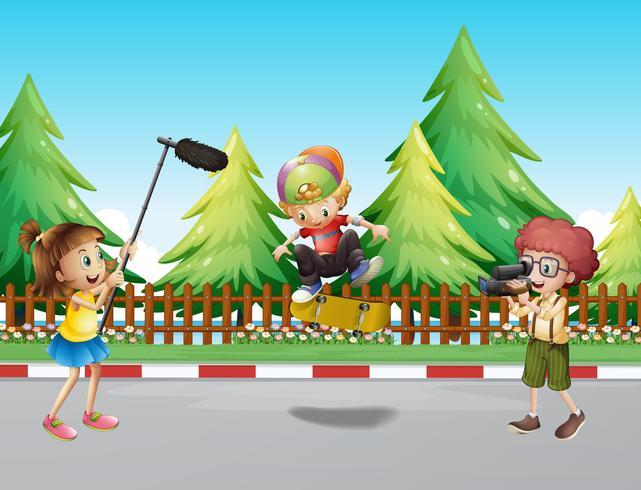 Children shooting boy playing skateboard