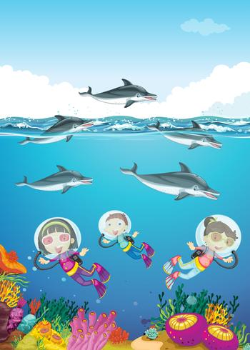 Dolfijnen en kinderen zwemmen onder de zee