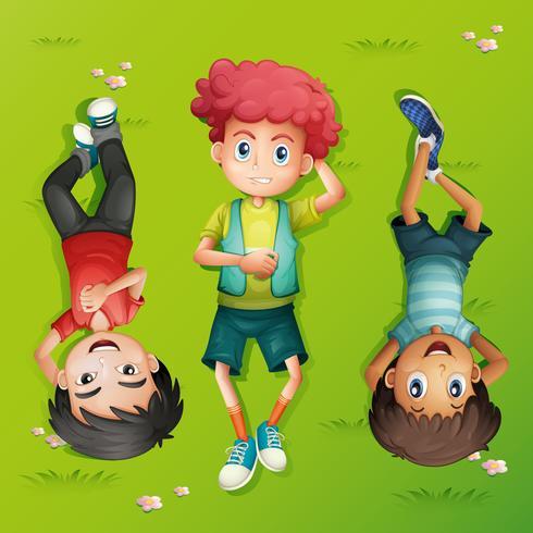 Tre barn ligger på gräsmattan