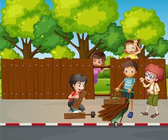 Många barn fixar trästaket tillsammans