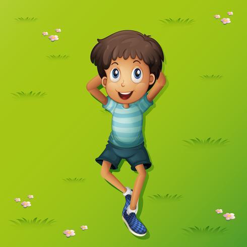 Feliz niño acostado en el pasto
