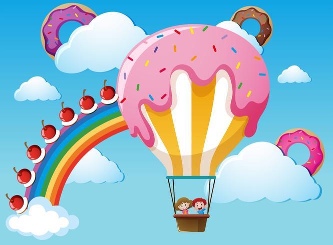 Scen med regnbåge och godisballong