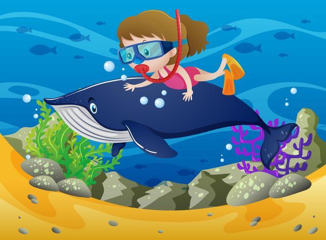 Fille plongeant avec une baleine sous la mer
