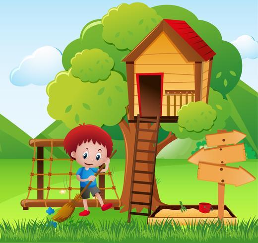 Little boy sweeping the garden