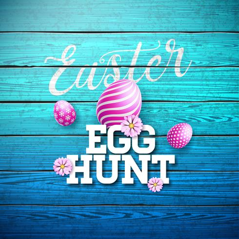 Ejemplo de la caza del huevo de Pascua con la flor y el huevo pintado en fondo de madera del vintage.