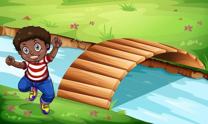 Un niño negro feliz cerca del puente de madera vector