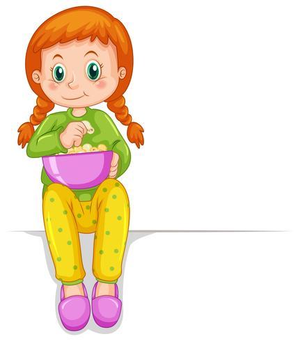 Liten flicka i pyjamas som äter popcorn