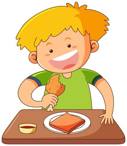 Glad pojke som äter på bordet