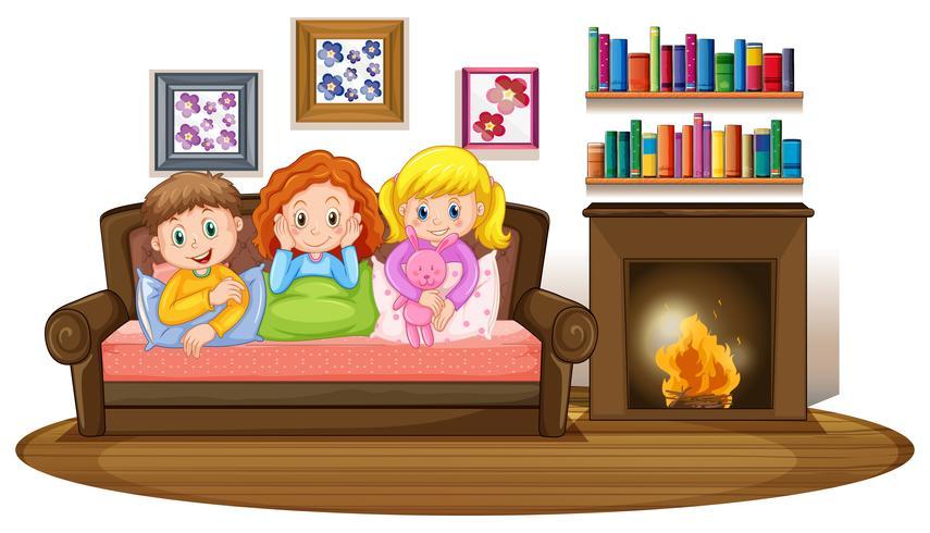 Tre barn på soffan vid eldstaden