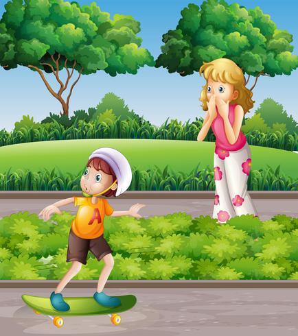 Garçon sur la planche à roulettes et mère dans le parc