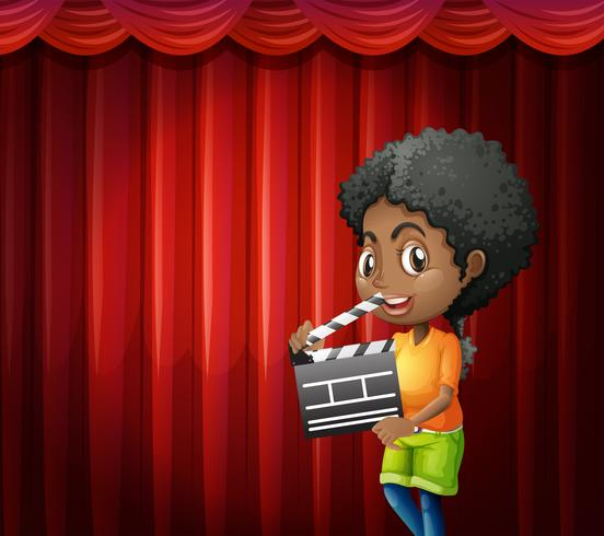 Girl holding clapboard in front of red curtain